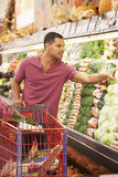Uomo che spinge carrello dal contatore dei prodotti in supermercato Fotografie Stock