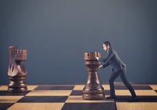 Uomo che spinge i pezzi degli scacchi Immagine Stock