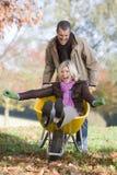 Uomo che spinge moglie in carriola Fotografie Stock