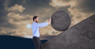 Uomo che spinge rotolamento intorno alla roccia fotografia stock