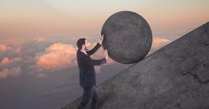 Uomo che spinge rotolamento intorno alla roccia fotografia stock libera da diritti