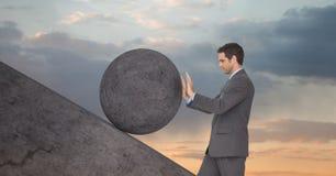 Uomo che spinge rotolamento intorno alla roccia immagini stock libere da diritti