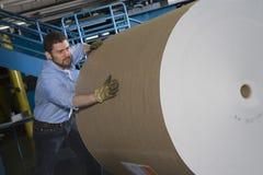 Uomo che spinge rotolo di carta enorme in fabbrica Immagini Stock
