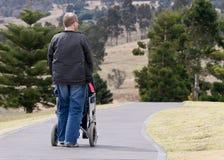 uomo che spinge sedia a rotelle Fotografia Stock