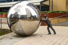 Uomo che spinge una palla enorme immagine stock