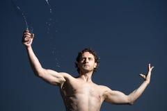 Uomo che spruzza acqua Fotografie Stock Libere da Diritti
