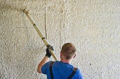 Uomo che spruzza stucco concreto per murare immagini stock libere da diritti