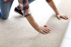 Uomo che srotola la nuova pavimentazione del tappeto immagini stock