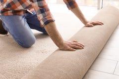 Uomo che srotola la nuova pavimentazione del tappeto Immagine Stock
