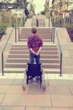 Uomo che sta con la sedia a rotelle davanti alle scale Fotografia Stock