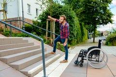 Uomo che sta con la sedia a rotelle davanti alle scale Fotografia Stock Libera da Diritti
