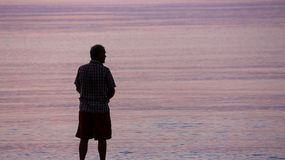 Uomo che sta da solo accanto al mare o al lago nelle prime ore del mattino Fotografia Stock