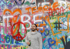 Uomo che sta davanti alla parete variopinta dei graffiti Immagine Stock