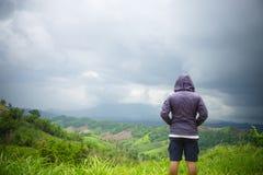 Uomo che sta sopra la collina della montagna Scalatore di libertà sull'alto va Fotografia Stock