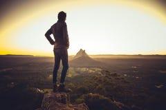 Uomo che sta sulla scogliera sopra la valle fotografia stock
