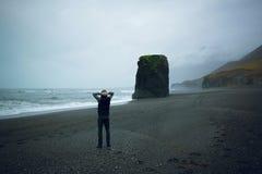 Uomo che sta sulla spiaggia di sabbia nera sull'Islanda Fotografie Stock