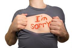 Uomo che stacca maglietta grigia Testo rosso sono spiacente scritto sulla h immagini stock