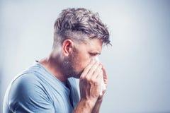 Uomo che starnutisce in un tessuto all'aperto Allergia del polline, primavera Fotografie Stock Libere da Diritti
