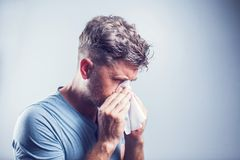 Uomo che starnutisce in un tessuto all'aperto Allergia del polline, primavera Fotografia Stock Libera da Diritti