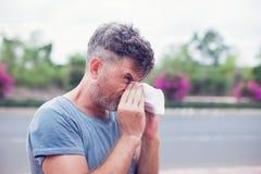 Uomo che starnutisce in un tessuto all'aperto Allergia del polline, primavera Immagine Stock Libera da Diritti