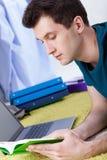 Uomo che studia sul pavimento Immagine Stock