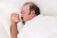 Uomo che succhia il suo pollice mentre dormendo Immagine Stock