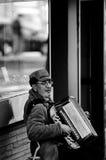 Uomo che suona per la strada per i soldi con la fisarmonica Immagini Stock Libere da Diritti