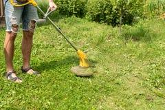 Uomo che taglia l'erba nel cortile con una falciatrice da giardino, regolatore, dettaglio Copi lo spazio immagini stock