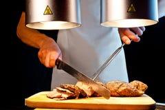Uomo che taglia la carne Fotografia Stock