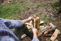 Uomo che taglia legno a pezzi nella foresta Fotografie Stock Libere da Diritti