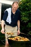 Uomo che tende barbecue Immagine Stock