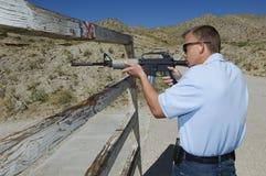 Uomo che tende fucile alla gamma di infornamento Fotografie Stock Libere da Diritti