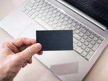 Uomo che tiene biglietto da visita nero in bianco Computer portatile su fondo, modello Fotografia Stock