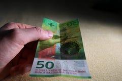 Uomo che tiene cinquanta franchi svizzeri alto vicino Fotografia Stock Libera da Diritti