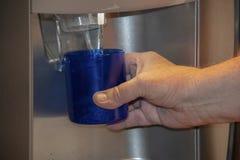Uomo che tiene classe sotto l'erogatore dell'acqua nella porta del frigorifero - il primo piano ha potato fotografia stock