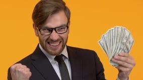 Uomo che tiene contanti a disposizione, esultanza della somma di denaro grande, alto deposito di interesse archivi video