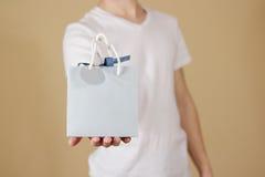 Uomo che tiene derisione in bianco disponibila della borsa del regalo della carta blu su Pac vuoto Immagini Stock Libere da Diritti