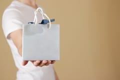 Uomo che tiene derisione in bianco disponibila della borsa del regalo della carta blu su Pac vuoto Fotografia Stock
