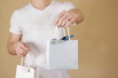 Uomo che tiene derisione di carta della borsa del regalo dello spazio in bianco due disponibili su Svuoti il pacchetto Immagine Stock Libera da Diritti