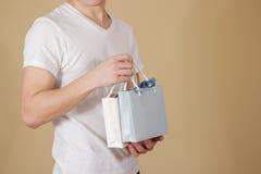 Uomo che tiene derisione di carta della borsa del regalo dello spazio in bianco due disponibili su Svuoti il pacchetto Immagine Stock