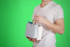 Uomo che tiene derisione di carta della borsa del regalo dello spazio in bianco due disponibili su Svuoti il pacchetto Fotografia Stock Libera da Diritti