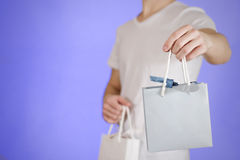 Uomo che tiene derisione di carta della borsa del regalo dello spazio in bianco due disponibili su Svuoti il pacchetto Fotografia Stock