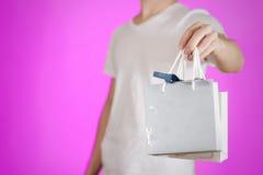 Uomo che tiene derisione di carta della borsa del regalo dello spazio in bianco due disponibili su Svuoti il pacchetto Immagini Stock
