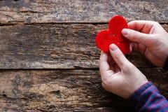 Uomo che tiene due metà di un cuore rotto fotografie stock libere da diritti