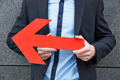 Uomo che tiene freccia rossa a sinistra Fotografia Stock