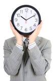 Uomo che tiene grande orologio che copre il suo fronte Immagini Stock Libere da Diritti