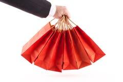 Uomo che tiene i sacchetti della spesa rossi Immagini Stock Libere da Diritti