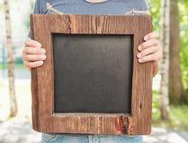 Uomo che tiene il bordo vuoto dell'ardesia e di legno Derisione del modello su fotografie stock libere da diritti