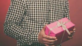 Uomo che tiene il contenitore di regalo rosa attuale Fotografie Stock Libere da Diritti