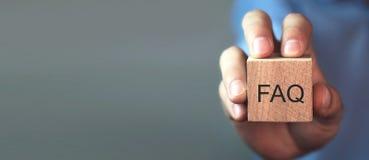 Uomo che tiene il messaggio del FAQ sul cubo di legno Domande frequentemente fatte immagini stock libere da diritti